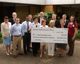 Scholarship recipients and representatives of the colleges of Medicine, Nursing and Health Related Professions join UAMS Chancellor I. Dodd Wilson, M.D., and John Blohm, UAMS vice chancellor for development and alumni affairs, in receiving a $94,500 check from the Arkansas Medical Society Alliance to endow future scholarships.