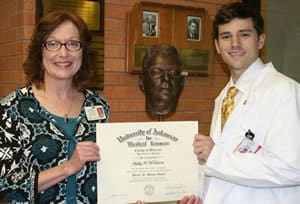 UAMS medical student Blake Williams received the Dr. Horace N. Marvin Award from Cynthia J.M. Kane, Ph.D., at Marvin's bust (center) in the UAMS Library.