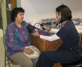 Sonia Bunyard, RN, gets a blood pressure measurement for a patient in the DeQueen clinic. Patients receive basic primary care through the clinic.