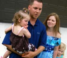 Brian and Jennifer Odle with their daughters Amelia (in Brian's arms) and Madelyn, talking about the cord blood transplant that treated Amelia's eye.