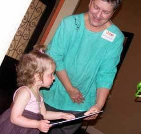 Michele Fox, M.D., presents Amelia Odle with a gift during a fundraiser for the Cord Blood Bank of Arkansas.