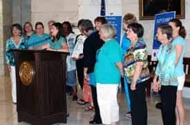 A group of ovarian cancer survivors gather at the podium.