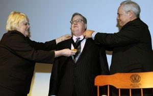 Dr. John Cone (center) is presented a medallion by Dean Debra Fiser (left) and Dr. Richard Turnage (right).