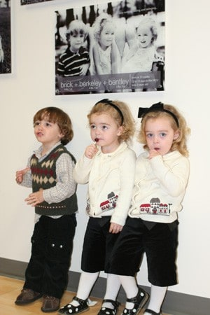UAMS NICU veterans Brick, Berkeley and Bentley, children of Curtis and Misty Fox of Gillett, pose beneath their picture.