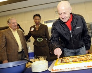 Myeloma Institute founder Dr. Bart Barlogie cuts a cake marking the 20-year anniversary of the institute. Eighteen-year survivor Ken Stoll (left) and the Institute's Sonja Rose look on.