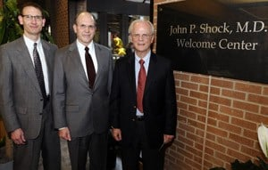Richard Harper, Christopher Westfall and John Shock stand near the entrance to the welcome center.