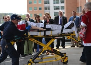 A simulated patient is rushed from an ambulance to the Simulation Center at the conclusion of the opening ceremony for a training demonstration inside.
