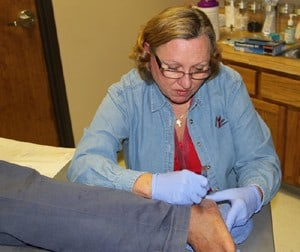 UAMS orthopaedic surgeon Ruth Thomas, M.D., examines a patient's feet at River City Ministry in North Little Rock.