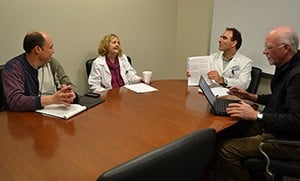 Mahmoud Kiaei, Ph.D., third from the left, shows Robert Griffin, M.D., left, Stacy Rudnicki, M.D., and John Crow, Ph.D., all of UAMS, a copy of a journal article detailing the results of ALS research in which he played a key role.