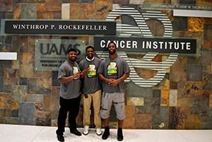 Clinton McDonald (left), Demetrius Harris (center) and Michael Johnson (right) visited the UAMS Winthrop P. Rockefeller Cancer Institute on April 3.