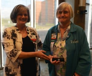 Melissa Fontaine, UAMS' chief operating officer, presents volunteer Edith Bowman with the UAMS Medical Center Volunteer Distinguished Service Award.