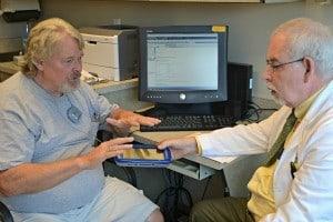 W. Steven Metzer, M.D., (right) performs the initial programming of Tommy Rickman's deep brain stimulator.