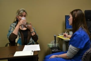 "Deleen Davidson performs ""cup bubbles"" breathing exercise for speech-language pathologist Hylan Pickett."