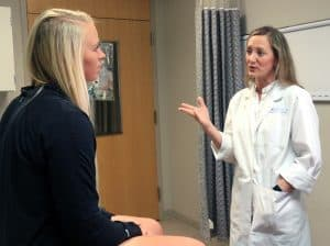 Theresa Wyrick, M.D., consults with patient Andrea Kindrick three months after surgery for cubital tunnel syndrome.