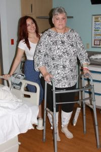 Jeanne Nash walks in her room as her daughter looks on.