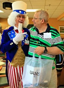 Uncle Sam (aka Glenn Ballard, director of University Rehabilitation Services) thanks former Army Medic Everette Heerboth for his military service while giving him a care package from UAMS employees.