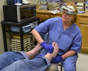 Karen Seale, M.D., checks a patient's feet for swelling during a Soles4Souls foot exam.