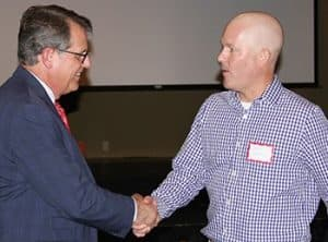 Peter Emanuel, M.D., executive director of the UAMS Winthrop P. Rockefeller Cancer Institute, shakes hands with Jared Woodard at the Jonesboro luncheon.