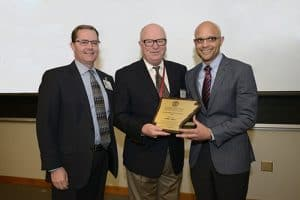 Jyric Sims, M.P.H., (right) receives an outstanding alumnus award for the Master of Health Administration program from MHA Alumni Association President Mike Perkins (left) and Richard Ault, M.H.S.A., MHA program director.