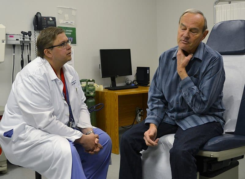 Robert Tunaitis shows Matthew Smeds, M.D., where his neck is tender following surgery to clear blockage from his carotid artery.