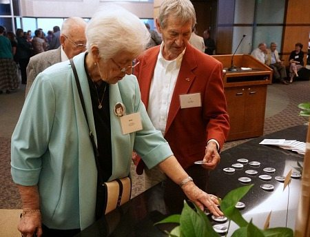 Drs. Betty and J. Ball, both COM '61 graduates, examine buttons featuring their classmates' Caduceus pictures.