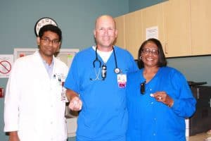 """Tim Trusty, R.N., (center) and Carol Harris, R.N., were awarded """"I Saved a Brain"""" pins by Sanjeeva Onteddu, M.D., for quickly getting Ricky Mays helps after he suffered a stroke."""