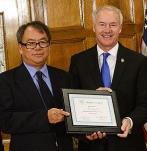 Hong-yu Li, Ph. D., left, receives his ARA Scholar certificate from Gov. Hutchinson.