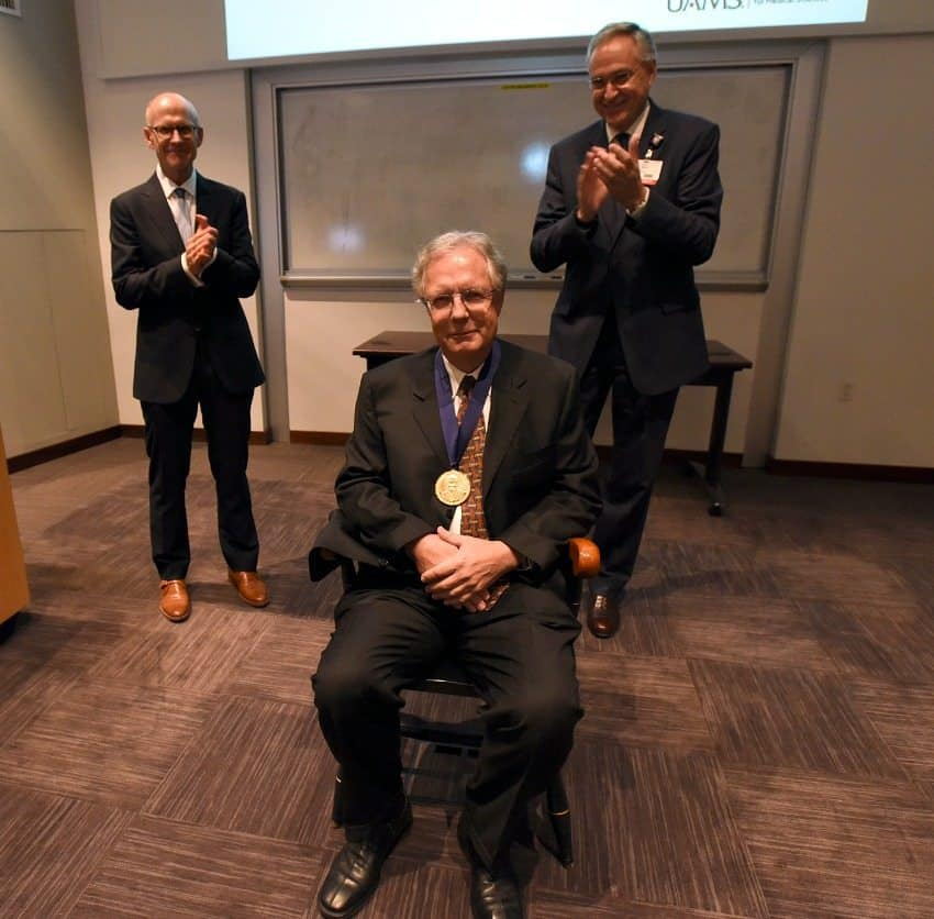 Martin Hauer-Jensen, M.D., Ph.D., is presented with a chair as part of the investiture ceremony, while College of Pharmacy Dean Keith M. Olsen, Pharm.D., and Chancellor Dan Rahn, M.D., look on.