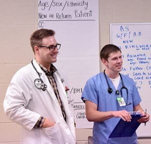 "Carson York, a PA student, and nursing student Colby Murphy present a ringworm case to the preceptors in the ""War Room"" at the 12th Street clinic."