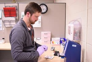 Adam Price, a third-year medical student, runs blood tests in the 12th Street clinic's laboratory.