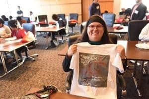 Student holding up T-shirt