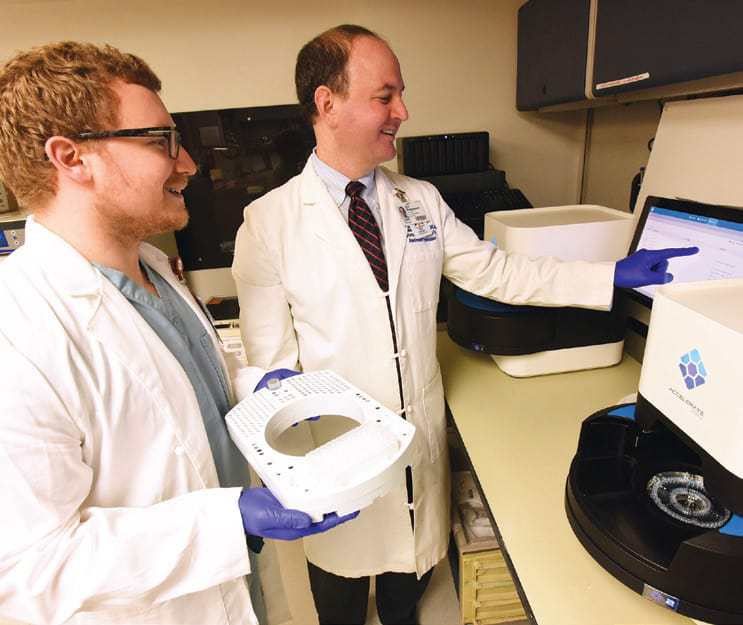 Eric Rosenbaum, M.D., M.P.H., (right) shows the Accelerate Pheno to resident Jonathon Gralewski, D.O., in the UAMS Clinical Microbiology Laboratory. The Accelerate Pheno identifies pathogens associated with blood-borne infections and the antibiotics most effective against them.