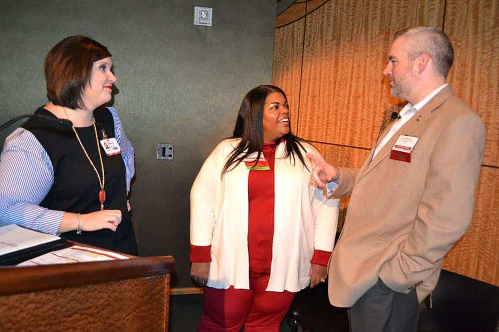 ohn Kirtley, right, talks with Laura Haywood, left and Lanita White, center, before making a presentation at the Pharmacy Update conference.