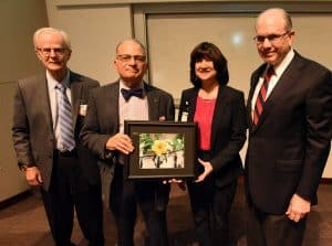 Kushner was presented a photograph of the gatehouse at the Hanoi Hilton by John P. Shock, M.D., JEI founding director; Stephanie Gardner, Pharm.D., Ed.D.; and Christopher Westfall, M.D., JEI director.