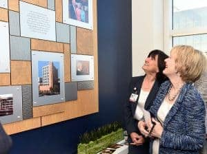 Interim UAMS Chancellor Stephanie Gardner, Pharm.D., Ed.D., and Nancy Shock, wife of John P. Shock, M.D., JEI founding director, share a laugh while viewing the new Walker Center placard on the newly renovated ninth floor of JEI.