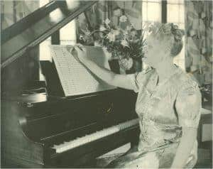 Price, photographed here in her St. Anne home, plays the piano. Photo Courtesy of Special Collections, University of Arkansas Libraries.