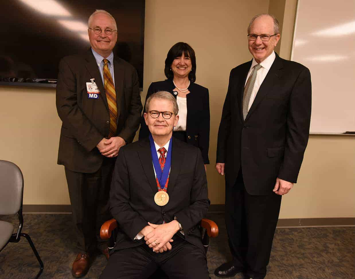 James McDonald, M.D. sits in the chair given to him as part of the investiture, shown here with (from left) Richard Turnage, M.D., UAMS Interim Chancellor Stephanie Gardner, Pharm.D., Ed.D., and Christopher Westfall, M.D.