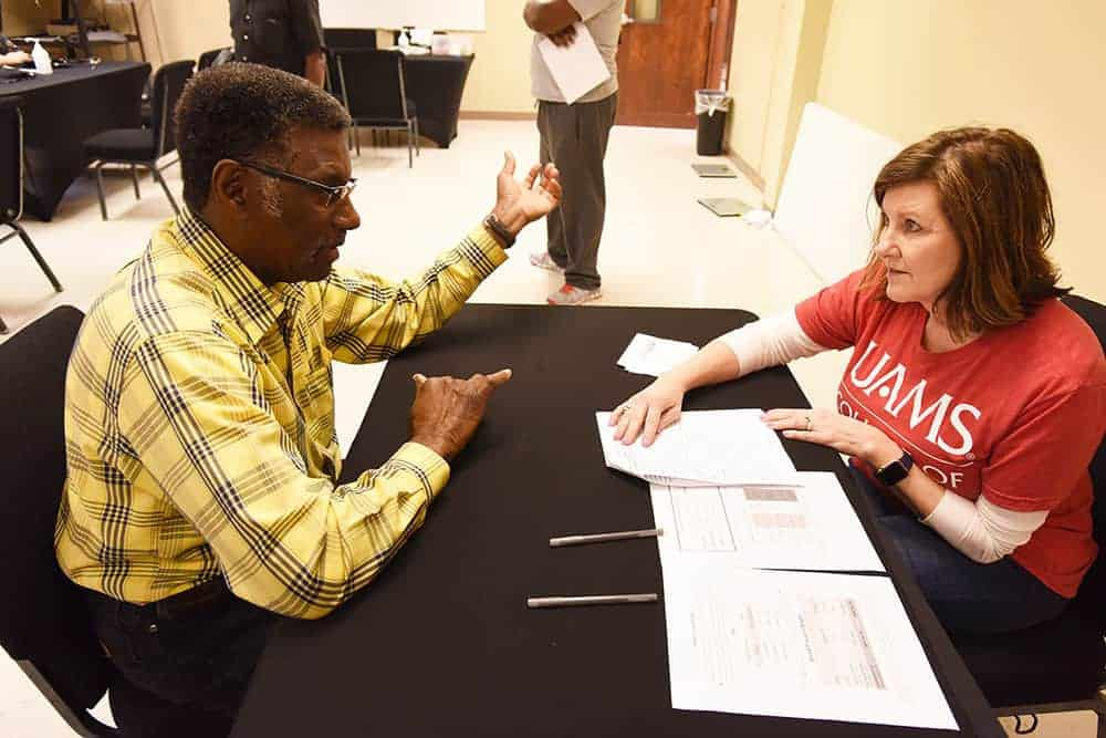 Patrick Pettus, left, talks with a volunteer at March Man-ness at Saint Mark Baptist Church. It was the second year Pettus attended the annual event.