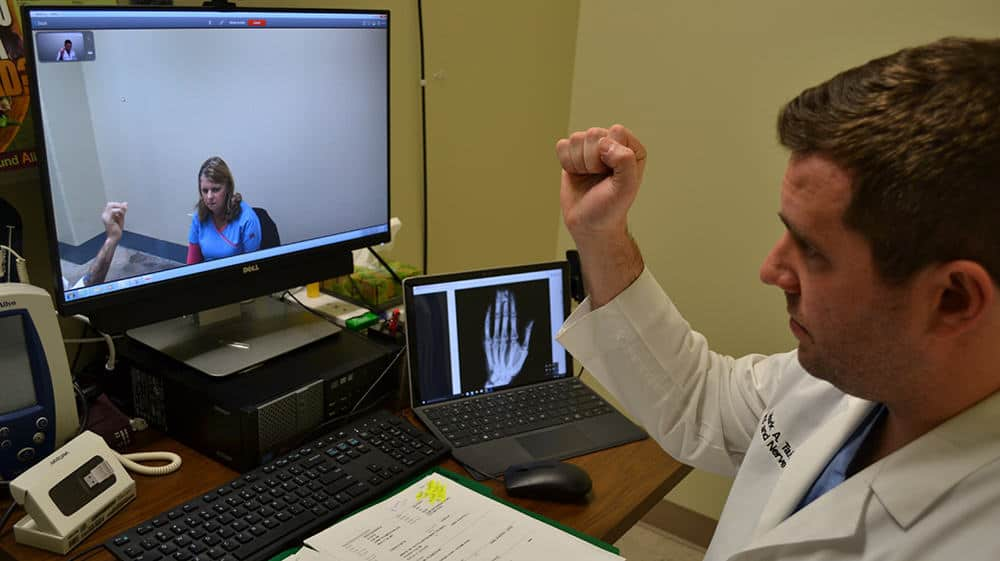 Orthopaedic surgeon Mark Tait, M.D., via a live video connection demonstrates to an Arkansas Department of Corrections inmate patient and a prison nurse how Tait wants him to make a fist as part of a medical examination.