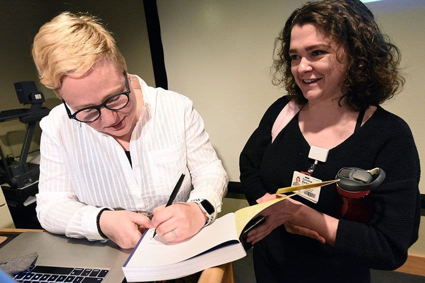 MK Czerweic, R.N., who uses the pseudonym Comic Nurse, signs a copy of her book for workshop participant Caroline Barham.