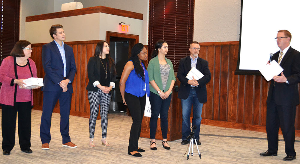 Nancy Gray, far left, gets ready to present prizes to the winning team at the Health Sciences Entrepreneurship Boot Camp in May.