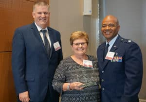 Nathan Johnson, Ph.D., poses for a photo with Cindy Osburn, who was presented with the MLS Outstanding Service Award, and with Air Force Lt. Col. Keye Latimer, who was presented with the MLS Distinguished Military Service Award.