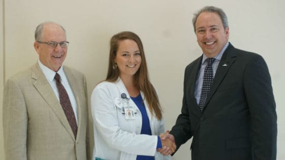 Third-year medical student Zoe Weeks (center), flanked by UAMS College of Medicine Dean Christopher T. Westfall, M.D., shakes hands with Corey Little, president of Arkansas Mutual Insurance Co.