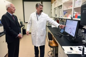 Donald Johann Jr., M.D., (right) shares information with Gov. Asa Hutchinson about his research into the potential of using liquid biopsies to detect lung cancer.