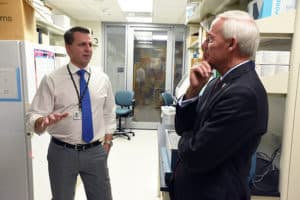 Alan Tackett, Ph.D., (left) discusses his melanoma research with Gov. Asa Hutchinson.