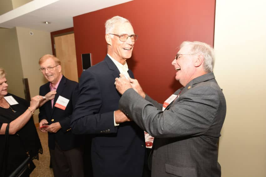 Jack Blackshear Jr., M.D., COM '68 (at right), pins a button on George Fielder Jr., M.D., COM '68 at the Friday night welcome reception.