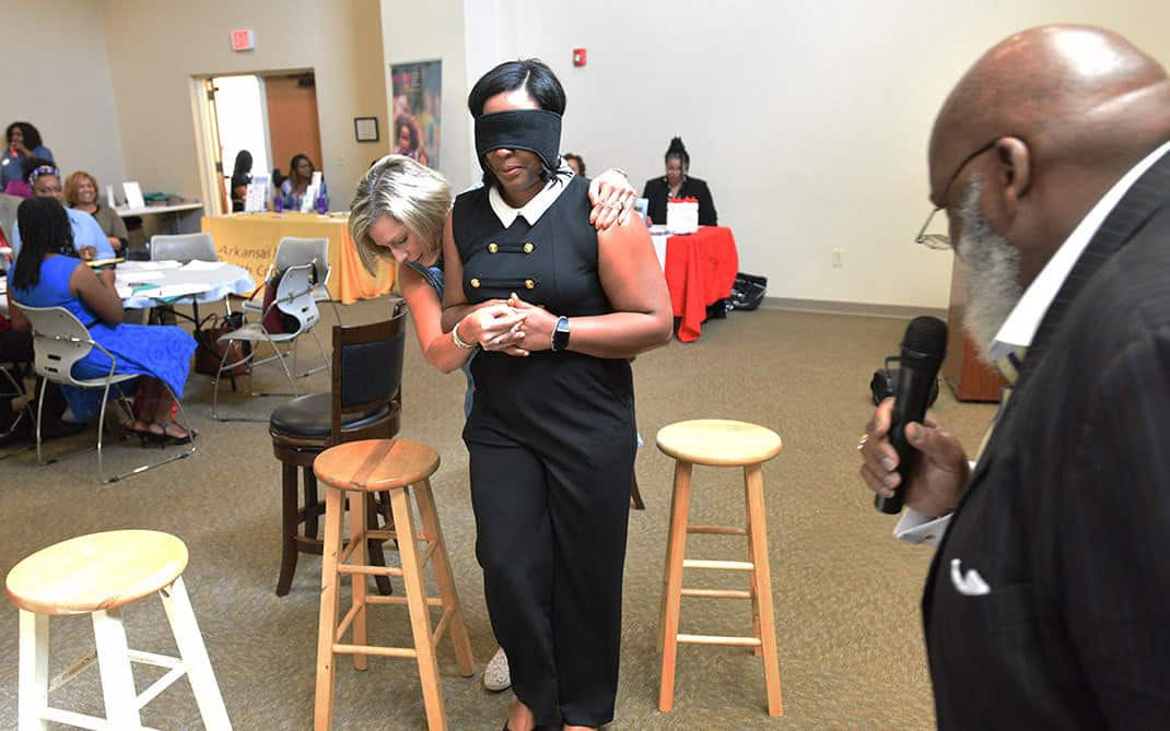 Kenneth O. Young, right, watches as Leanne Lefler guides a blindfolded volunteer from the audience through an obstacle course at the FAITH Network Summit.