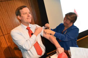 Chancellor Cam Patterson, M.D., MBA, gets his flu shot during his Sept. 17 Town Hall meeting.