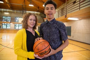 Bishop pauses on the basketball court for a photo with his mother, Angela Copeland