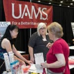 UAMS staff visit with one of the attendees at the Senior Expo at the Statehouse Convention Center.